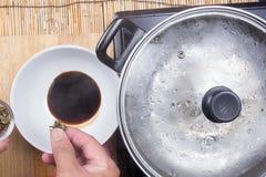 Шеф-повар положил сухую морскую водоросль к соевому соусу Стоковое Изображение