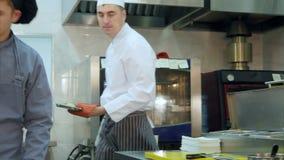 Шеф-повар получая испеченных рыб от печи, пока его тренирующая подготавливая плиту сток-видео