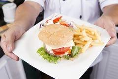 Шеф-повар представил плиту гамбургера Стоковые Изображения RF