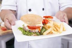 Шеф-повар представил плиту гамбургера Стоковые Фото