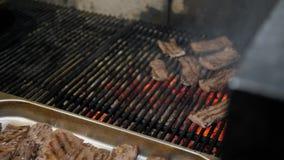 Шеф-повар принимает законченные стейки от гриля Пламена и красный гриль Аргентины тлеющих углей Подготовка огня и гриля для сток-видео