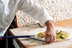 Шеф-повар принимая тесто пиццы к кашевару стоковое изображение
