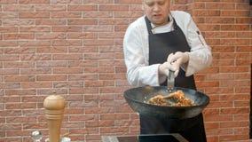 Шеф-повар пробуя блюдо и кладя соль к лотку Стоковые Изображения RF