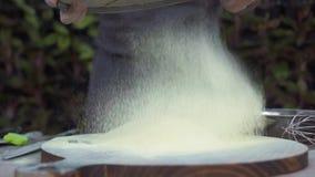 Шеф-повар просеивая порошок муки через сетку для печь замедленного движения Мука мужской руки лить на деревянной доске через сетк акции видеоматериалы
