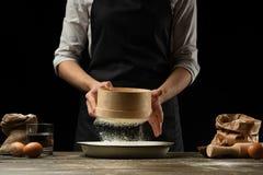 Шеф-повар работает с мукой, для варить focaccia, итальянские макаронные изделия, пиццу или хлеб Замерзать в движении Концепция ре стоковые изображения