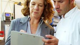 Шеф-повар разговаривая при работодатель держа доску сзажимом для бумаги сток-видео