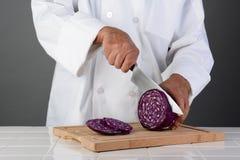 Шеф-повар режа голову красной капусты Стоковое Фото