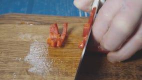 Шеф-повар режет красный пеец в малых частях сток-видео