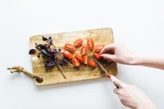 Шеф-повар режет томаты Взгляд сверху, белая предпосылка стоковое изображение