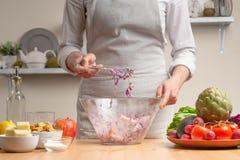 Шеф-повар смешивает салат, шевелит, в процессе вегетарианского салата в домашней кухне Светлая предпосылка для меню ресторана стоковое изображение rf