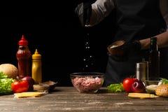 Шеф-повар соля семенить мясо для создания пирожка бургера На фоне с ингредиентами для бургера Гастрономия, рецепты, стоковое изображение rf