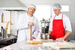 Шеф-повар стоя при коллега подготавливая равиоли стоковое фото rf