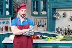 Шеф-повар с татуированной и пересеченной рукой в поло Укомплектуйте личным составом в красной рисберме Стоковое фото RF