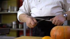 Шеф-повар точить нож в коммерчески кухне для варить тыкву акции видеоматериалы