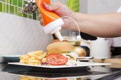 Шеф-повар украсил салат гамбургера, француза зажаренный и vegetable Стоковая Фотография