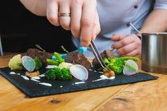 шеф-повар украшает плиту Стоковое Фото