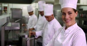 Шеф-повар усмехаясь на камере с командой за ей видеоматериал