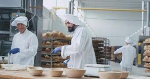 Шеф-повар хлебопека фабрики пекарни восторженный танцуя пока подготавливающ тесто для печь танцы хлеба и слушать видеоматериал