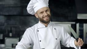 Шеф-повар человека имеет потеху с ножами на кухне Усмехаясь шеф-повар точить пересек ножи акции видеоматериалы