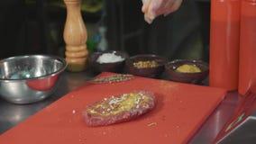 Шеф-повар marinating сырое мясо для подготавливать стейк на коммерчески кухне, конце-вверх акции видеоматериалы