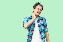 Шея или боль в спине Портрет грустного раненого молодого человека в случайном голубом checkered положении рубашки и держателя и у стоковые изображения rf