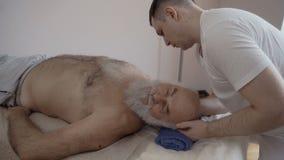 Шея массажа Masseur старика в slowmotion сток-видео
