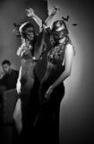 Шикарная дама с длиной плотными платьем и маской перед большим зеркалом стены, крытой съемкой Загадочный представлять молодой жен Стоковые Фото