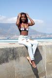 Шикарная африканская женщина в джинсах и бикини на пляже Стоковые Изображения RF