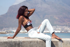 Шикарная африканская женщина в джинсах и бикини на пляже Стоковое Изображение