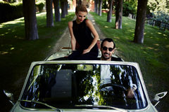 Шикарная богатая женщина чувствует настолько радостной пока они катание на cabriolet с уверенным красивым человеком брюнет Стоковое Изображение