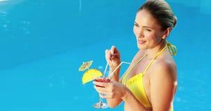 Шикарная блондинка в бикини наслаждаясь poolside коктеиля видеоматериал