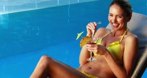Шикарная блондинка в бикини наслаждаясь poolside коктеиля акции видеоматериалы