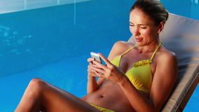 Шикарная блондинка в бикини отправляя СМС на poolside телефона сток-видео