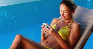 Шикарная блондинка в бикини отправляя СМС на poolside телефона видеоматериал
