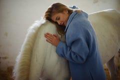 Шикарная дама в голубом пальто обнимает белую лошадь Стоковое Изображение RF