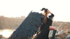 Шикарная дама с темной душой, ферзь восхода солнца ночи наблюдая, девушка в длинном светлом черном платье с черными крыльями пера акции видеоматериалы