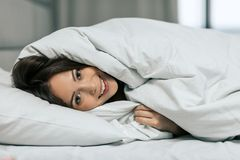 Шикарная девушка создавая программу-оболочку в теплом одеяле стоковое фото