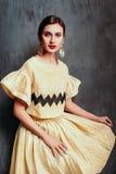 Шикарная девушка одетая в желтом красивом костюме стоковая фотография