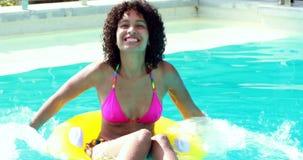 Шикарная женщина в бассейне брызгая в раздувном кольце видеоматериал
