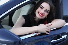Шикарная женщина в элегантном платье представляя в роскошном автомобиле Стоковая Фотография