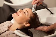 Шикарная женщина имея ее волосы быть помытым парикмахером стоковые фото