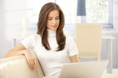 Шикарная женщина на софе с компьтер-книжкой стоковые изображения rf