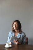 Шикарная женщина сидя внутри помещения используя планшет Стоковые Фото