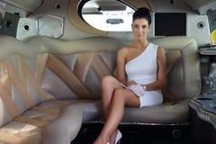 Шикарная женщина сидя в роскошном лимузине стоковое изображение rf
