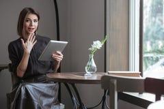 Шикарная женщина сидя около окна в кафе используя таблетку Стоковые Изображения