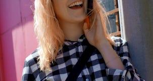 Шикарная женщина с кофейной чашкой говоря на мобильном телефоне outdoors 4k акции видеоматериалы