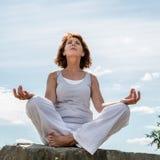 Шикарная зрелая женщина йоги работая outdoors на камне Стоковые Фотографии RF