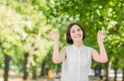 Шикарная и красивая бизнес-леди держит ее руки на уровне ее головы и усмехается пока в зеленом парке стоковое изображение