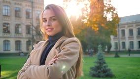 Шикарная кавказская женщина смотрит камеру пока стоящ холодок и усмехающся счастливо в sunlights, городской предпосылке видеоматериал
