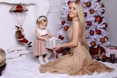 Шикарная мать при длинные светлые волосы представляя с прелестным милым d Стоковые Фотографии RF